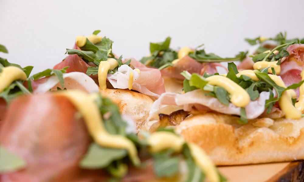 Focaccia con cipolle, prosciutto crudo, senape e rucola, Tossini